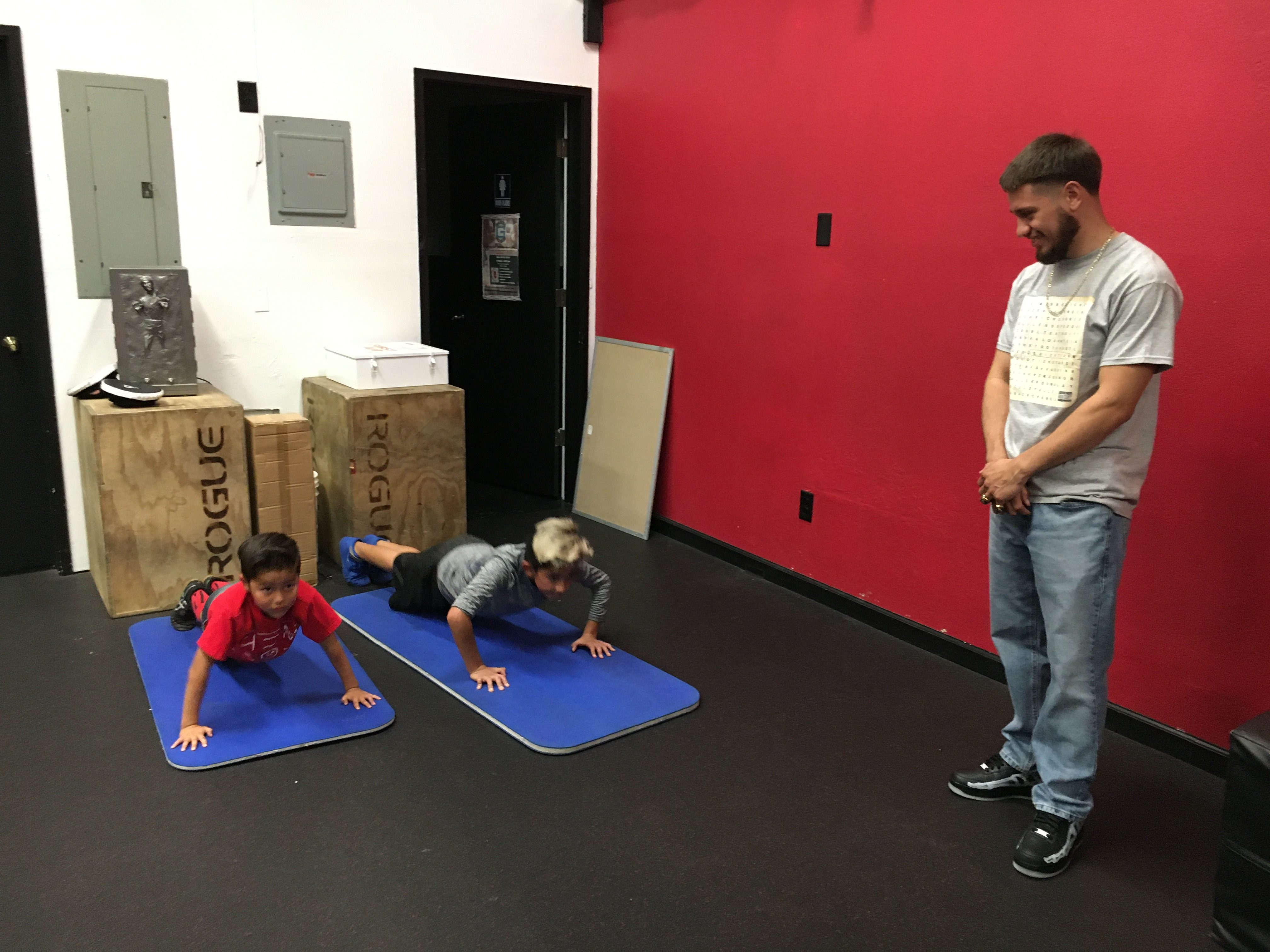 Ruben-Villa-IV-encourages-10-year-old-Isaac-Mendoza-AKA-Blondie-and-7-year-old-Joshua-Vallejo-Leprechaun-who-work-out-daily-at-his-gym.-DENNIS-TAYLOR-PHOTO-e1574882320455