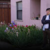 Young man standing in front of a light pink house with a bed of multi-colored roses blooming beside him