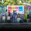 People on stage performing music, including a saxophonist, drummers and guitarists